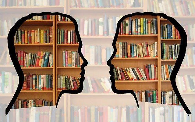 Twarze skierowane do siebie, w tle regały książek.