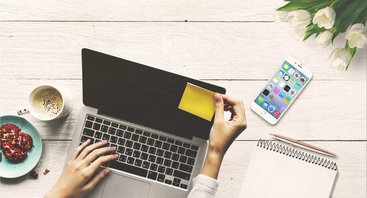 Laptop, telefon, karteczka, notes, przekąska, tulipany. Na zdjęciu widoczne ręce trzymające karteczkę.